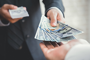 Man in a suit handing cash to an awaiting hand, representing ideal business influx. A Blog Post image concept