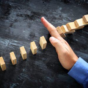A male hand stopping the domino effect. executive and risk control concept.