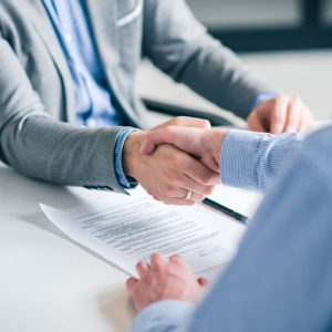 Investment banker is shaking hands with a client who has partnered with JD Merit to sell his mid-market company.